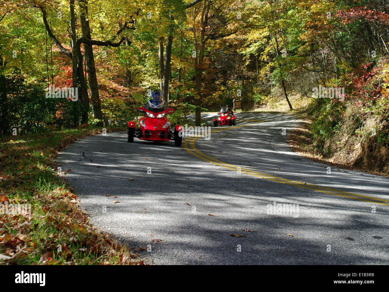 Two Can-Am motorized tricycles ride in the Sosbee Cove area, on Georgia's State Road 180, at the peak of Autumn. - Stock Image