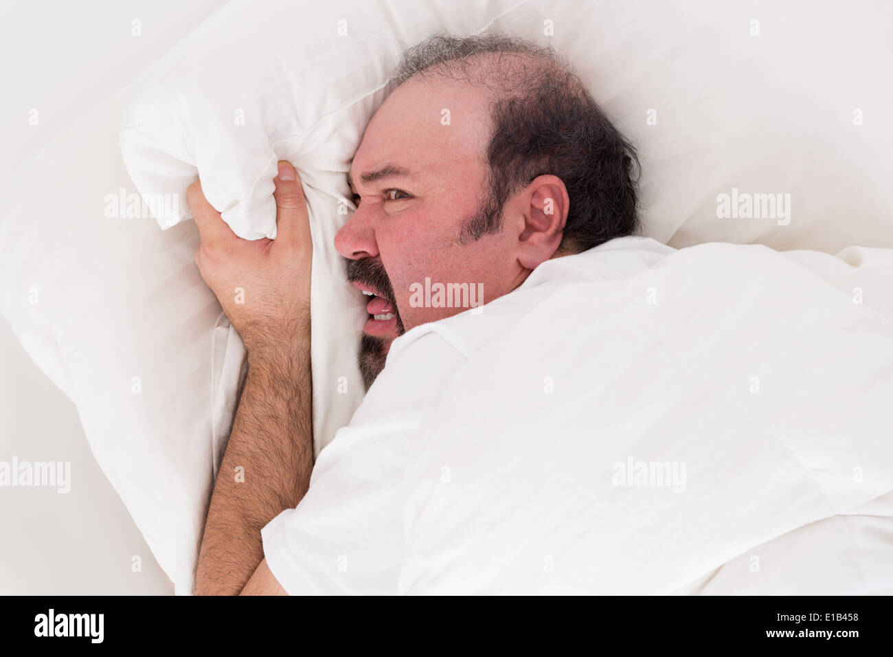 Insomniac clutching at his pillow in desperation as he balefully refuses to get up in the morning after a sleepless night - Stock Image