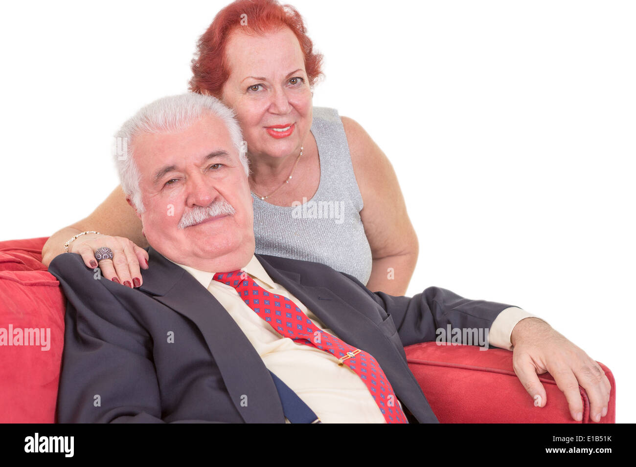 Loving elderly couple relaxing together on a red couch with the wife sitting behind her husband with her arm around his shoulder - Stock Image