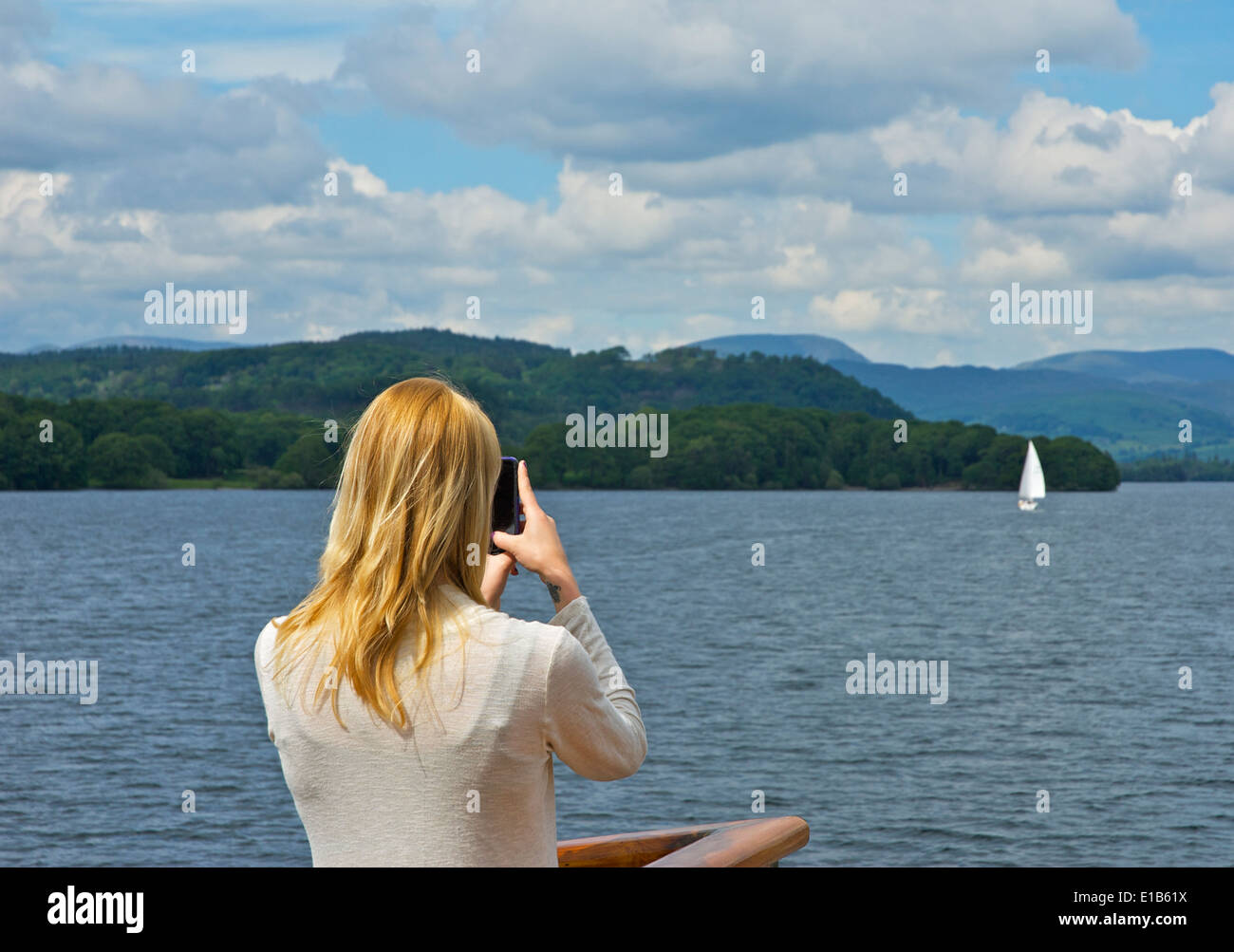 Young woman on passenger 'steamer', taking a photograph on smartphone, Lake Windermere, Lake District, Cumbria, England UK - Stock Image