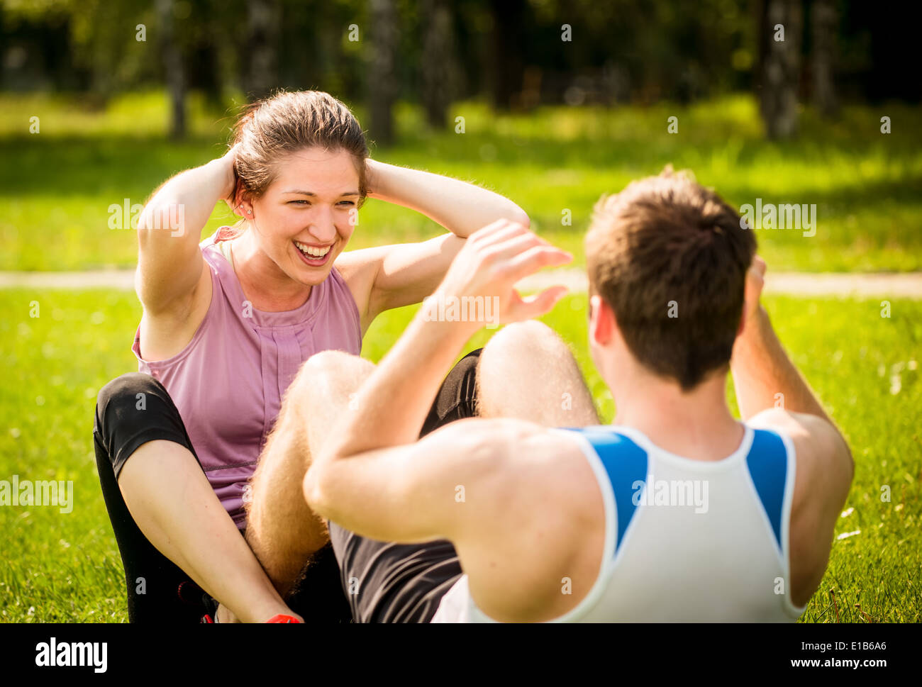 Sport couple making sit-ups together in nature on green grass - Stock Image