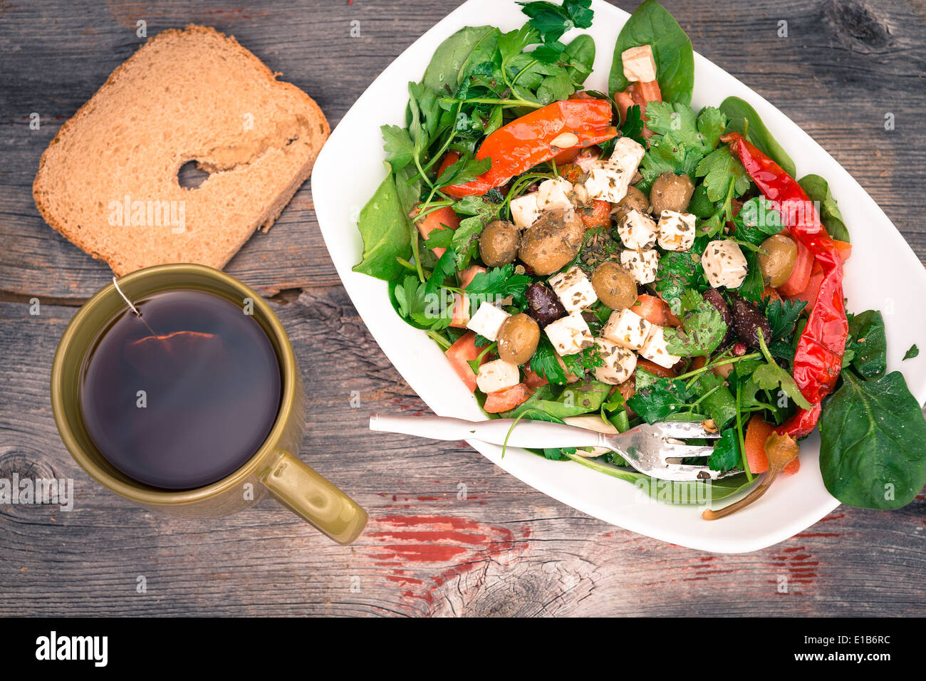 Overhead view of a dish of delicious fish leafy green baby spinach salad with bread and tea on a rustic wooden surface - Stock Image