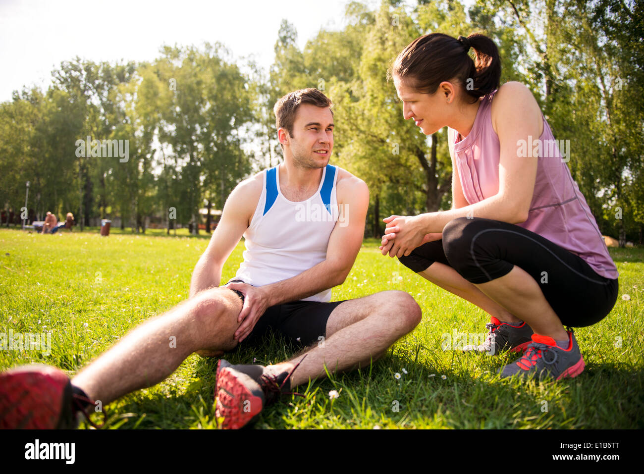 Woman is helping to young man with injured thigh from sport activity - Stock Image
