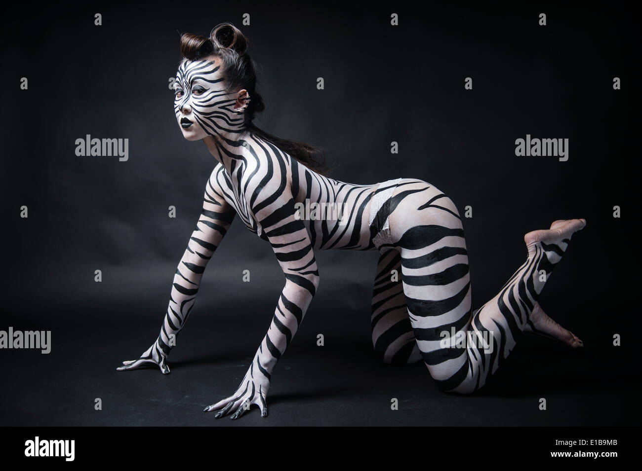 A woman with her body painted in black and white zebra stripes on her hands and knees like an animal