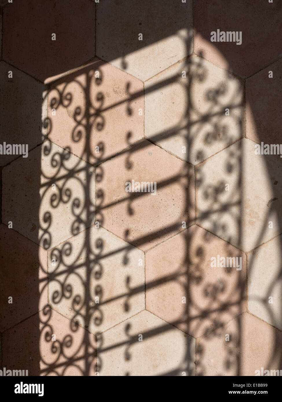 Shadow pattern of wrought iron screen on hexagonal ceramic floor tiles - Stock Image
