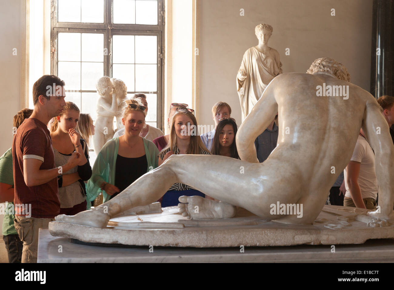 Visitors on a guided tour of the Musei Capitolini ( Capitoline Museum ), looking at the statue of the Dying Gaul,  Rome Italy - Stock Image