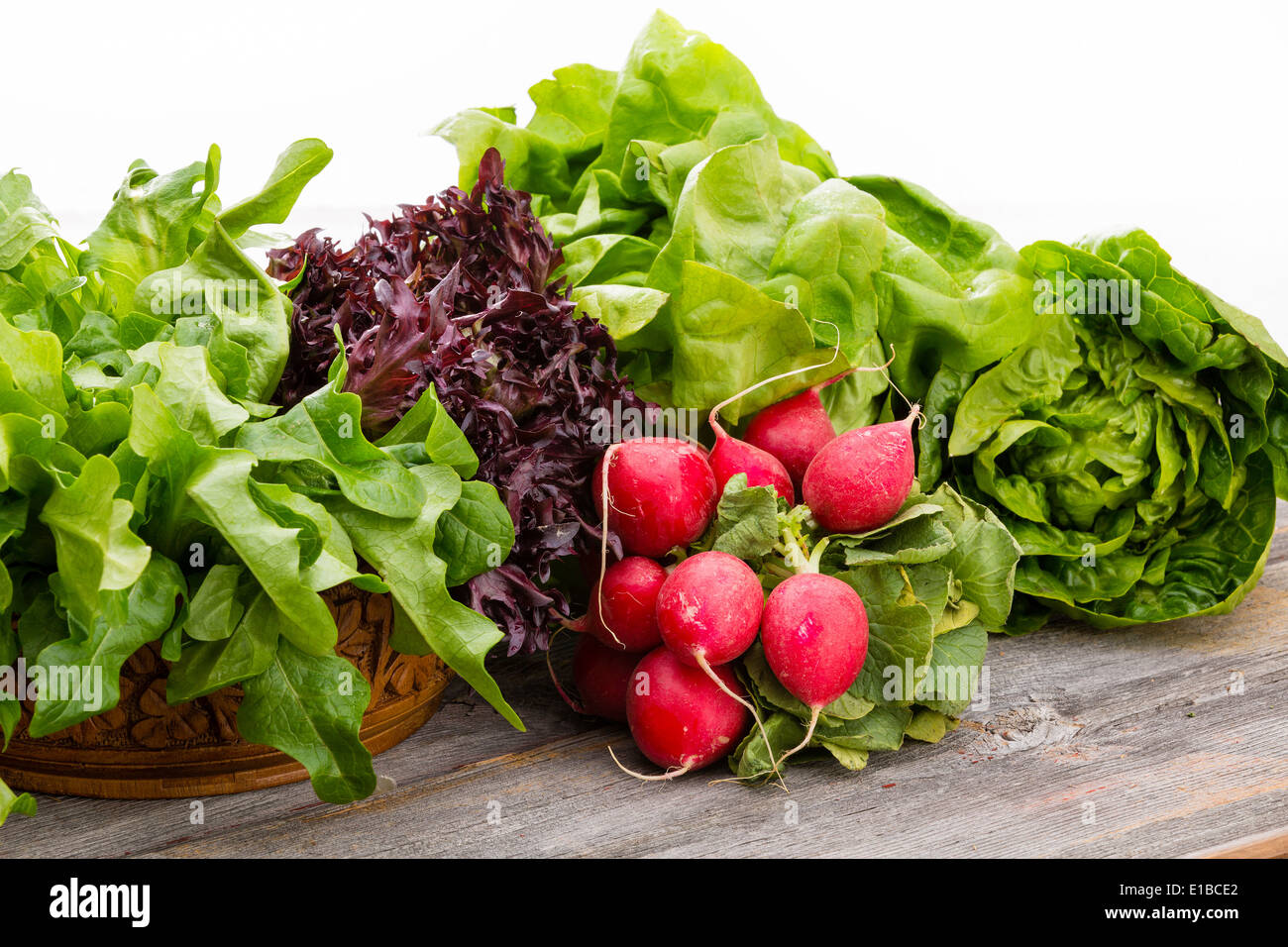 Healthy fresh salad ingredients displayed on old weathered wooden boards with several varieties of leafy green lettuce and a bun - Stock Image