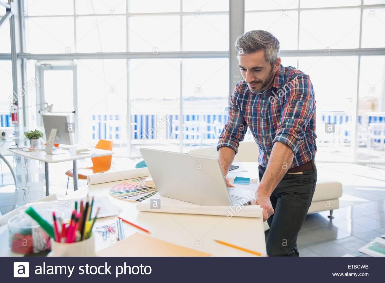 Creative businessman at laptop in office - Stock Image