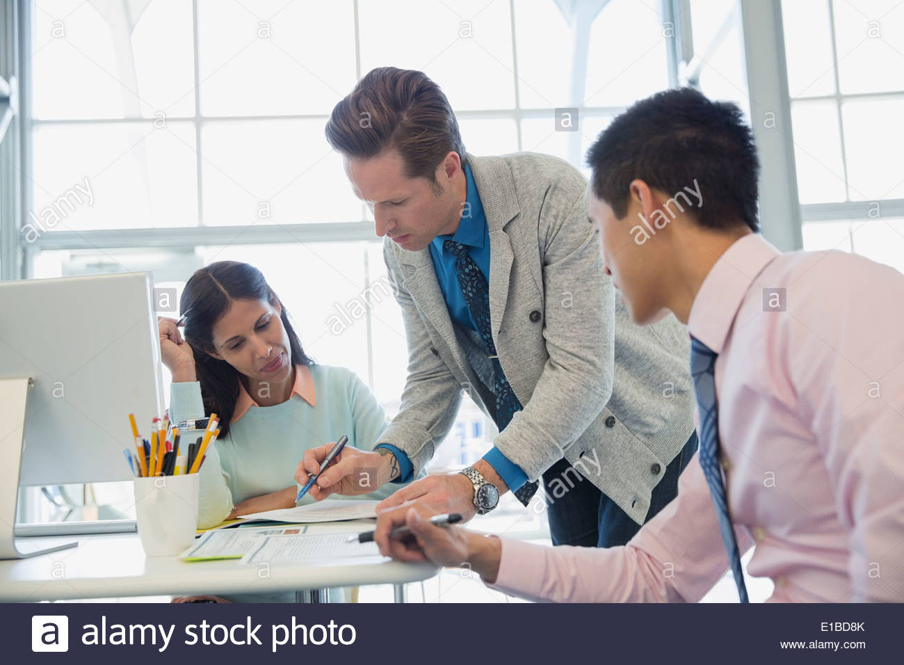 Business people meeting at desk in office - Stock Image