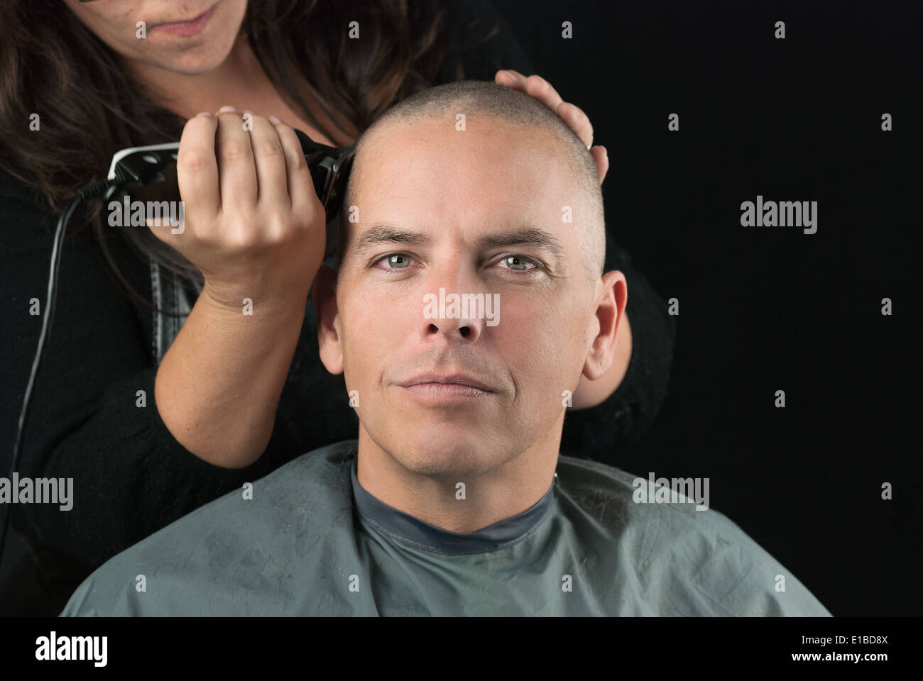 Close-up of a hair stylist using clippers to shave her Clients head. - Stock Image