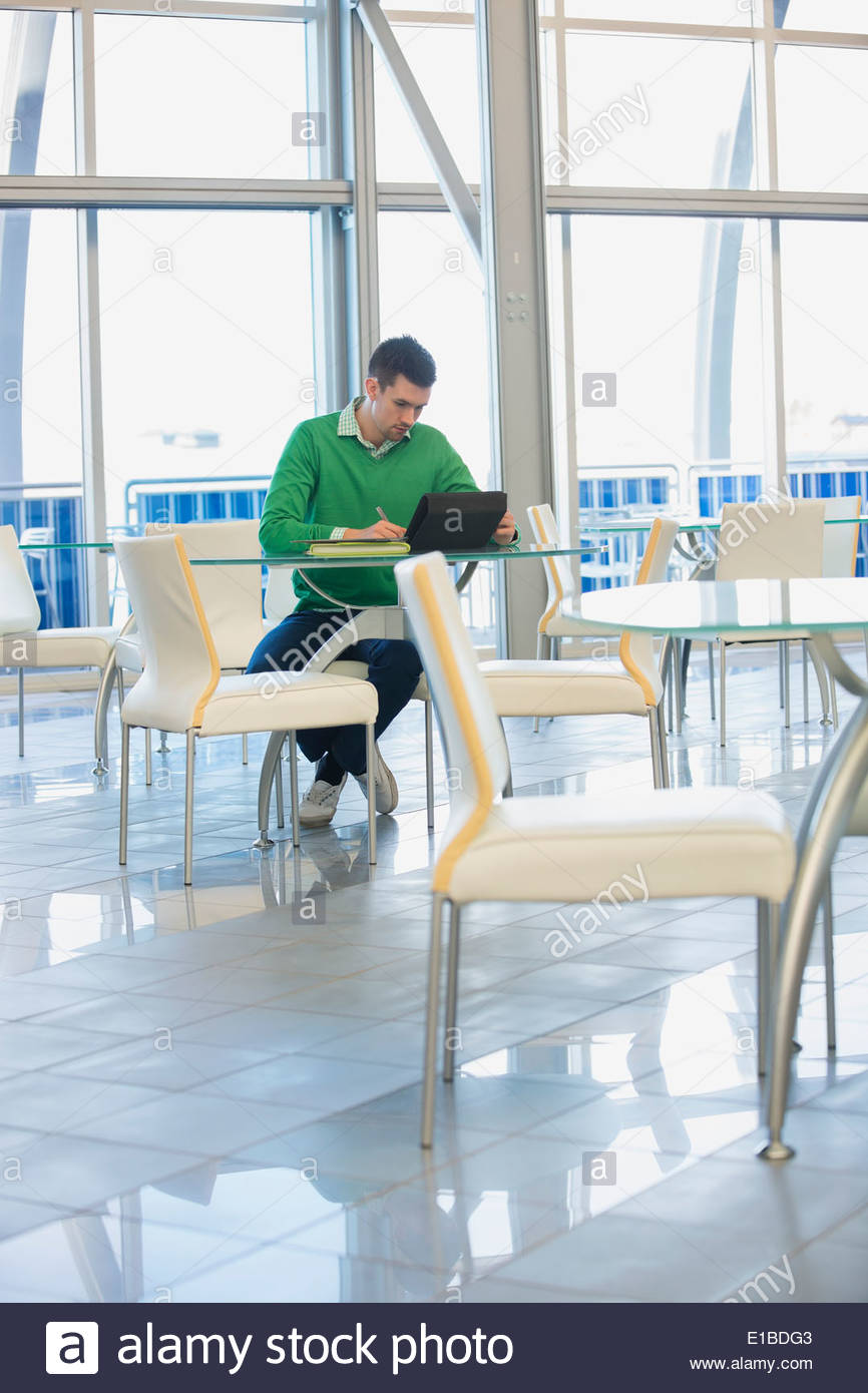 Businessman with digital tablet working in office cafeteria - Stock Image