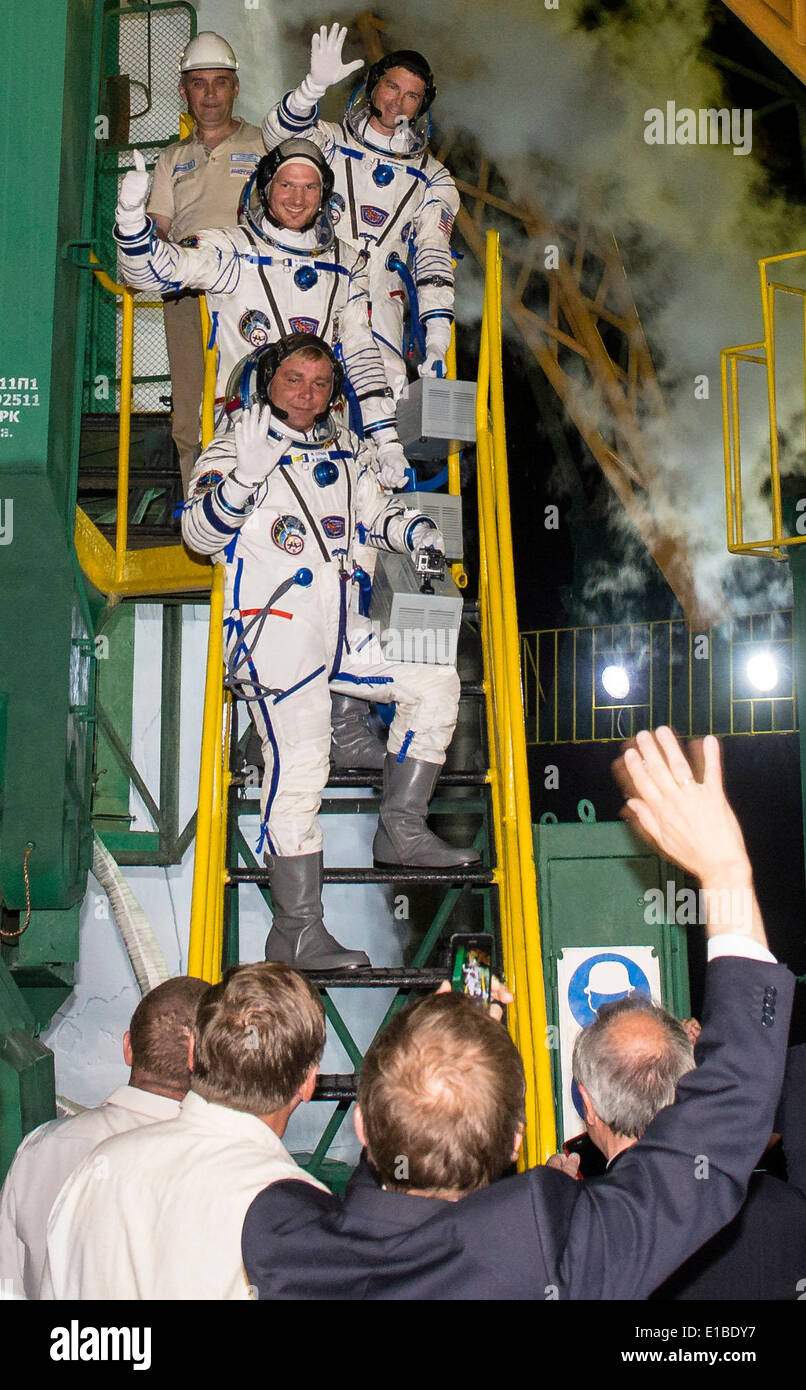 International Space Station Expedition 40 Soyuz Commander Maxim Suraev of the Russian Federal Space Agency, Roscosmos, bottom, Flight Engineer Reid Wiseman of NASA, center, and Flight Engineer Alexander Gerst of the European Space Agency, ESA, top, wave farewell prior to boarding the Soyuz TMA-13M rocket for launch May 28, 2014 at the Baikonur Cosmodrome in Kazakhstan. Suraev, Gerst, and Wiseman will spend the next six months aboard the International Space Station. - Stock Image