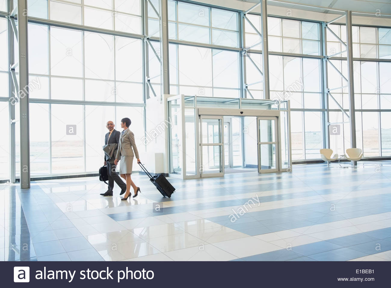 Business people with suitcases in modern lobby - Stock Image