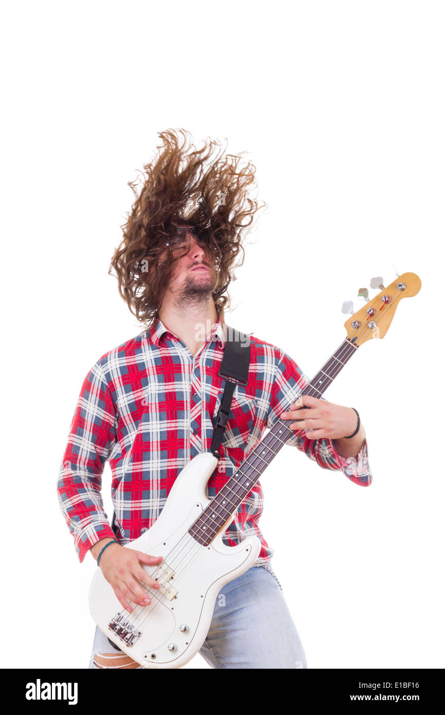 adult man in red shirt with tousled hair playing electric bass guitar - Stock Image