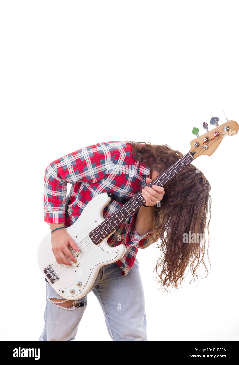 man in red shirt with tousled hair playing electric bass guitar - Stock Image