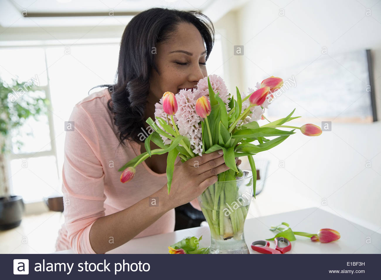 Woman smelling bouquet of flowers - Stock Image