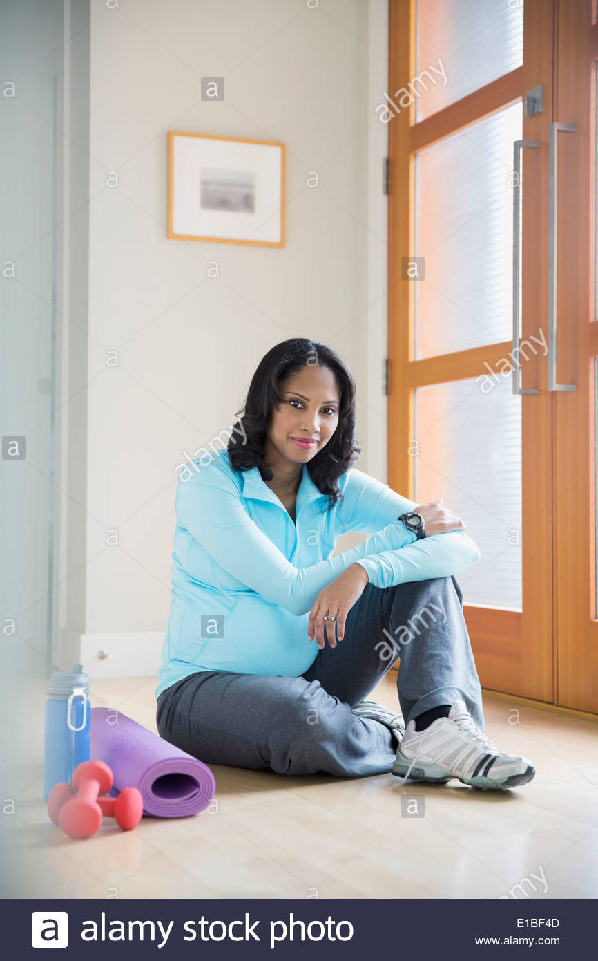 Portrait of pregnant woman with yoga mat - Stock Image