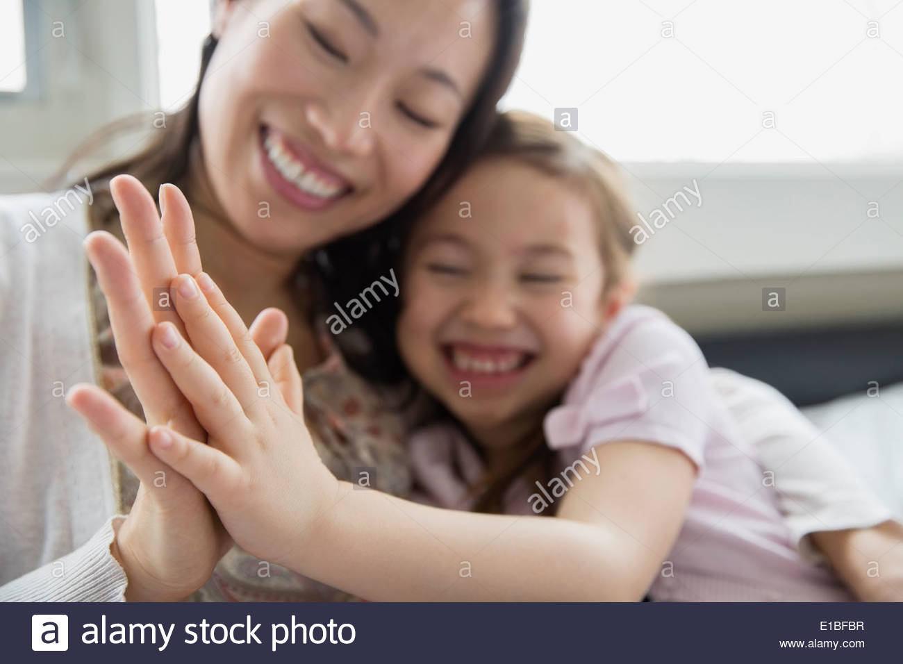 Mother and daughter touching hands - Stock Image