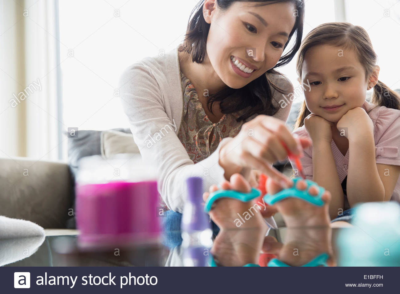Mother and daughter doing pedicures at home - Stock Image