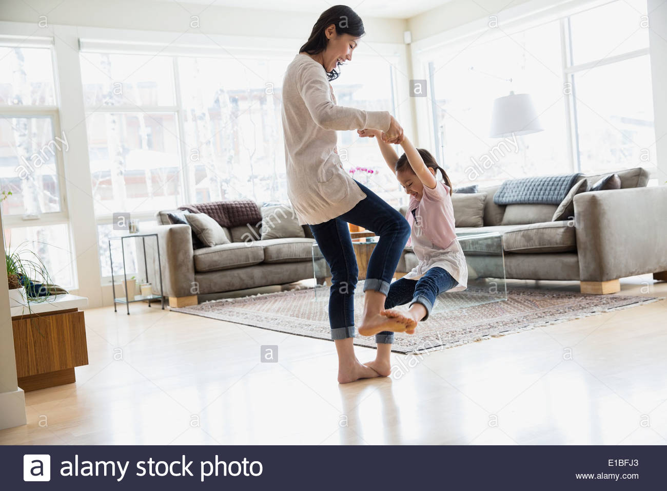 Daughter dancing on mothers feet in living room - Stock Image