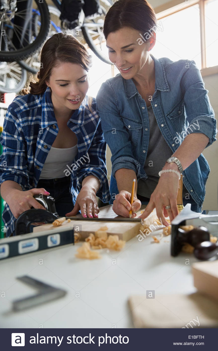 Mother and daughter woodworking in garage - Stock Image