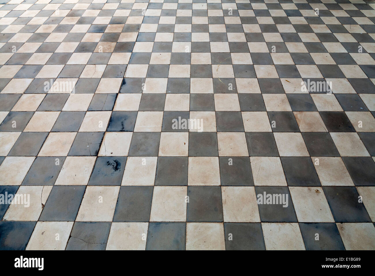 Close up of antique ceramic checkerboard tiled flooring with light shining across - Stock Image