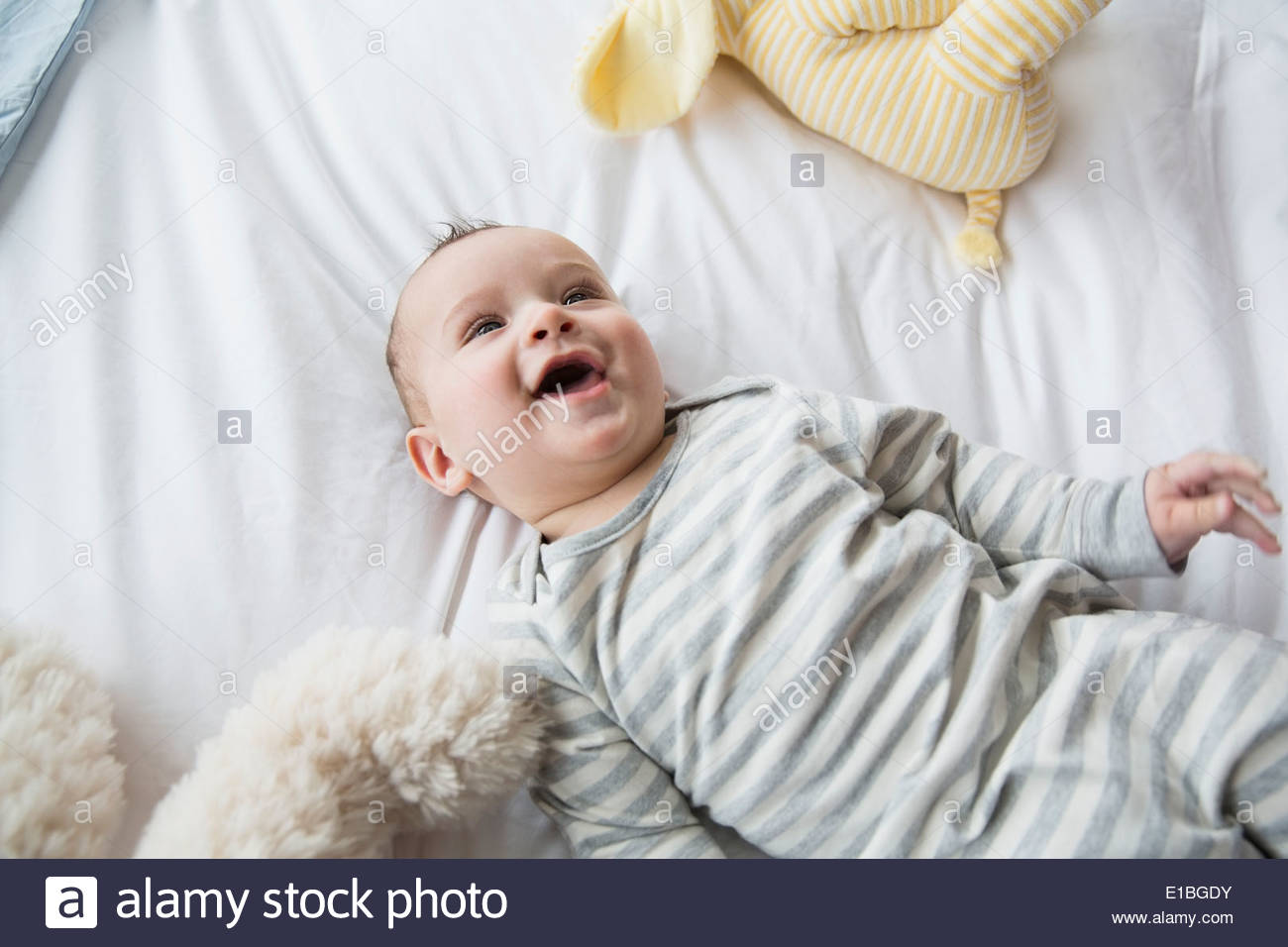 Laughing baby laying on bed - Stock Image