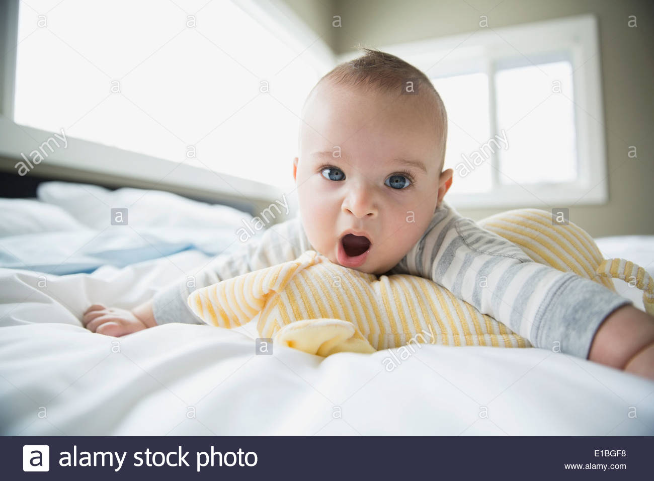 Portrait of yawning baby on bed - Stock Image