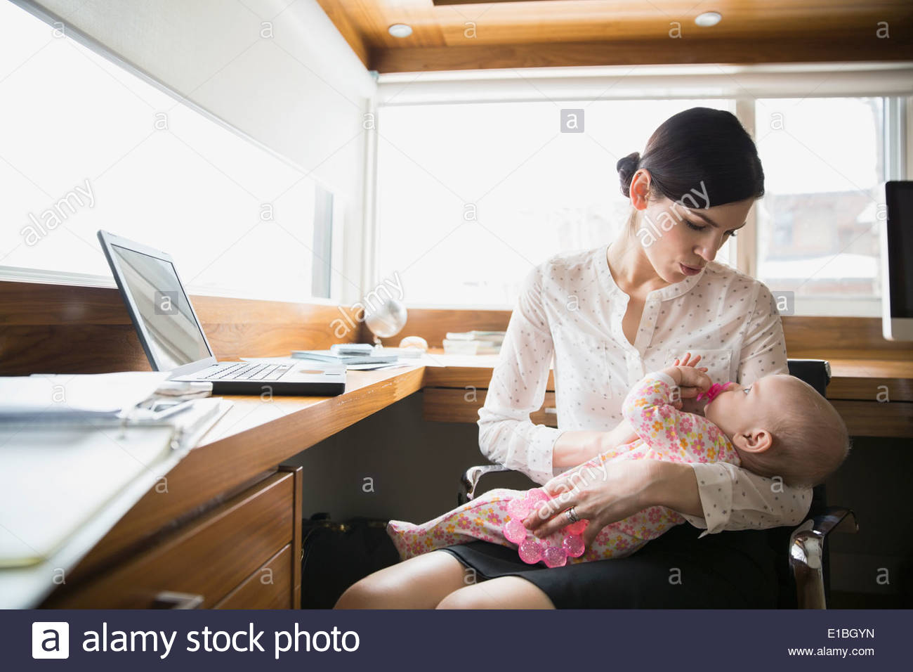 Mother holding baby in home office - Stock Image