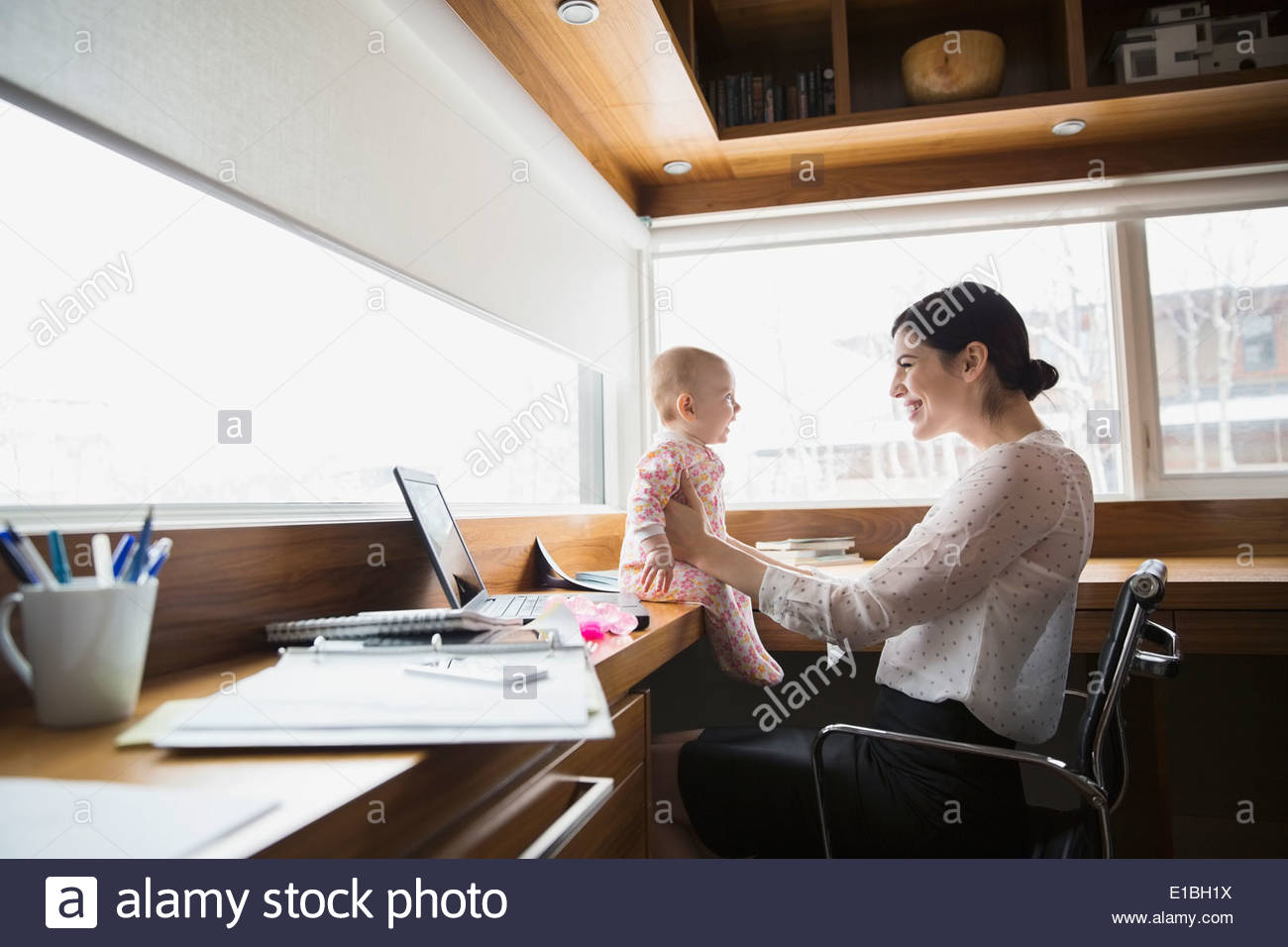 Mother and baby at laptop in home office - Stock Image