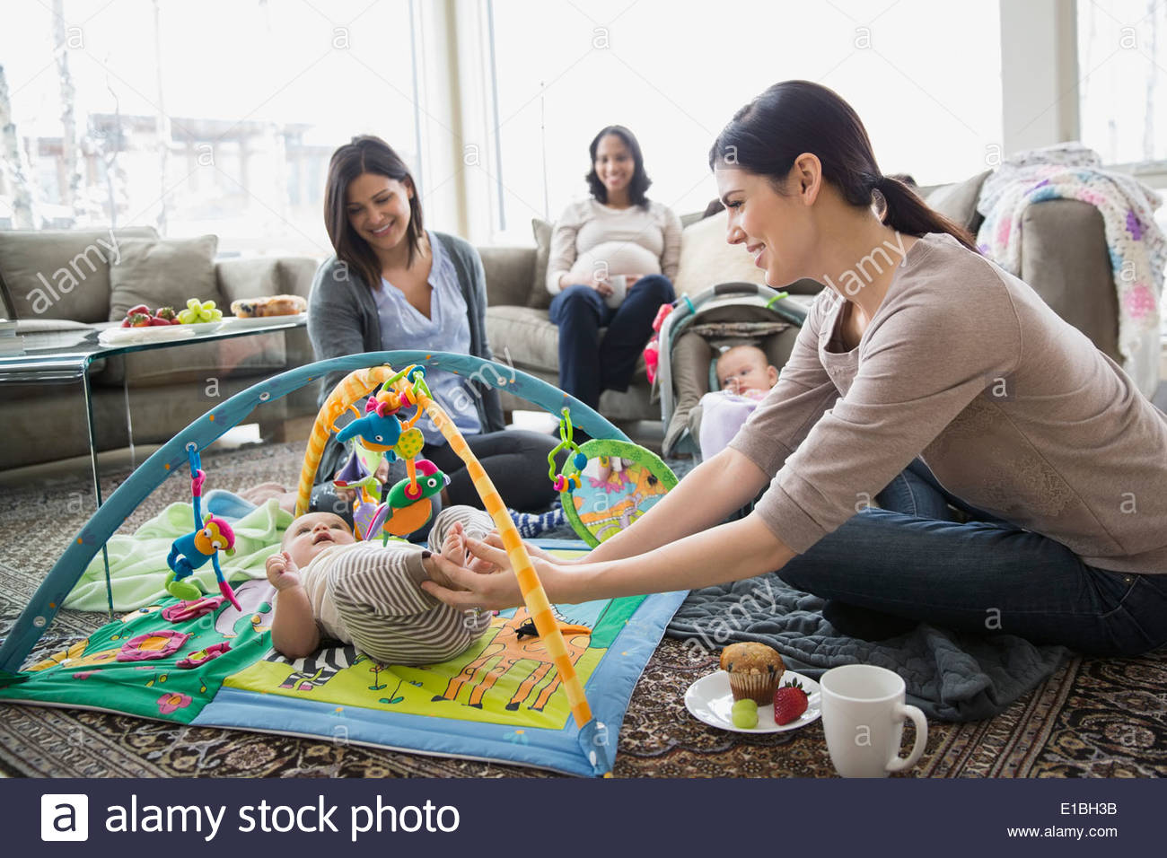 Mothers and babies in living room - Stock Image
