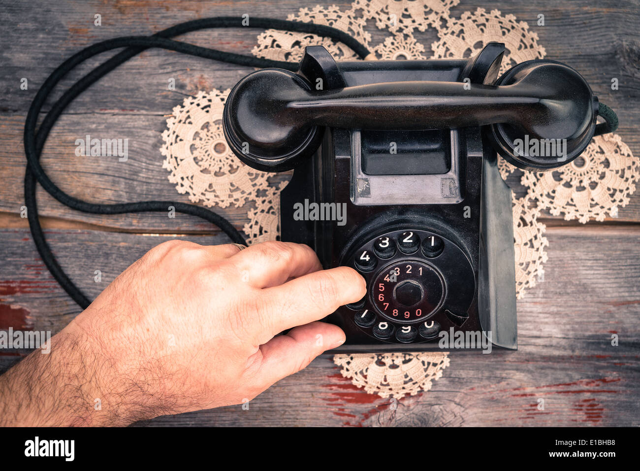 Man making call on rotary telephone dialing the numbers with his finger high angle view of the instrument on an old wooden table - Stock Image