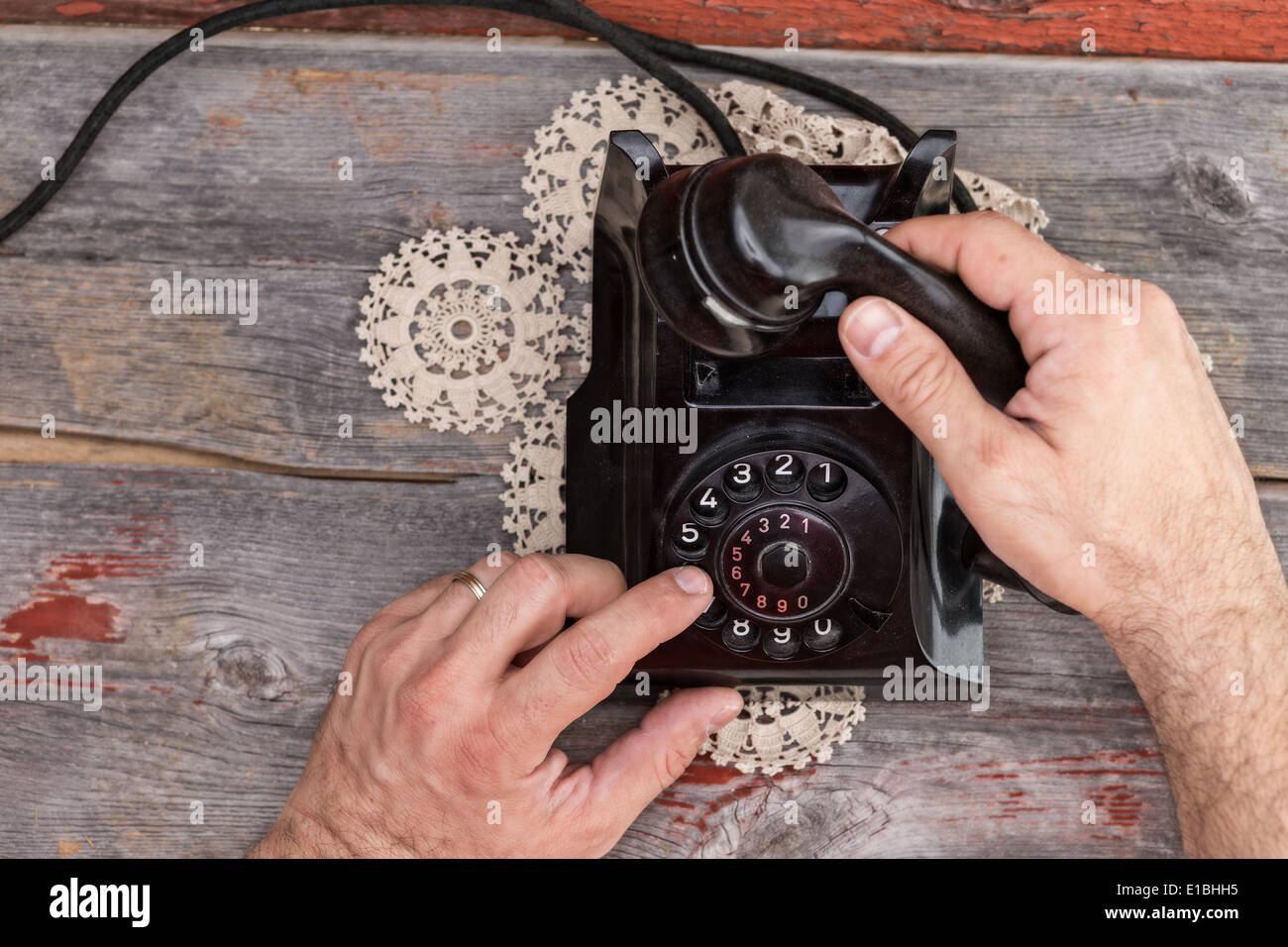 High angle view of the hands of a married man dialing out on an old rotary telephone standing on a weathered rustic table top - Stock Image