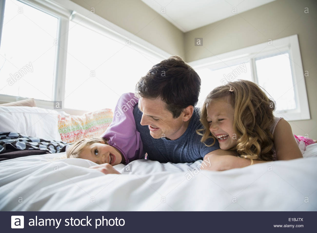 Father and daughters playing on bed - Stock Image