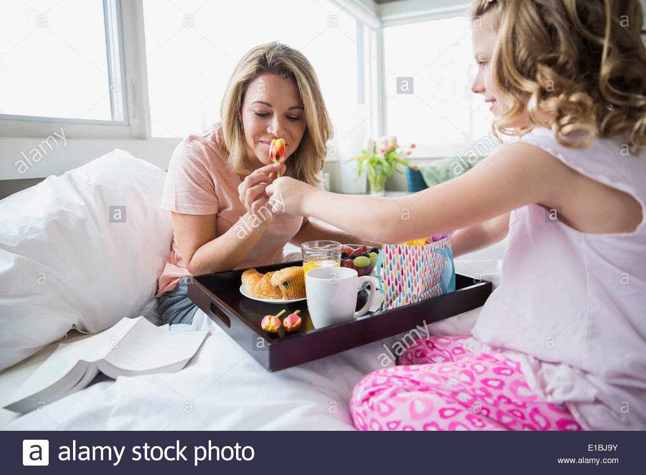 Daughter bringing breakfast to mother in bed - Stock Image