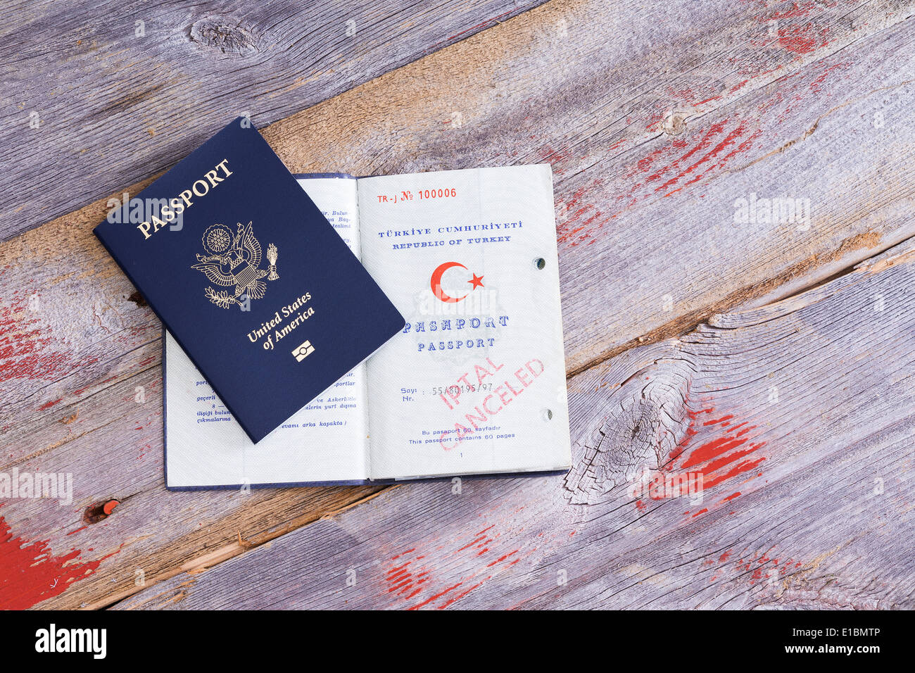 An American and Turkish passport lying on an old wooden table with the Turkish passport opened to reveal a canceled hand stamp - Stock Image