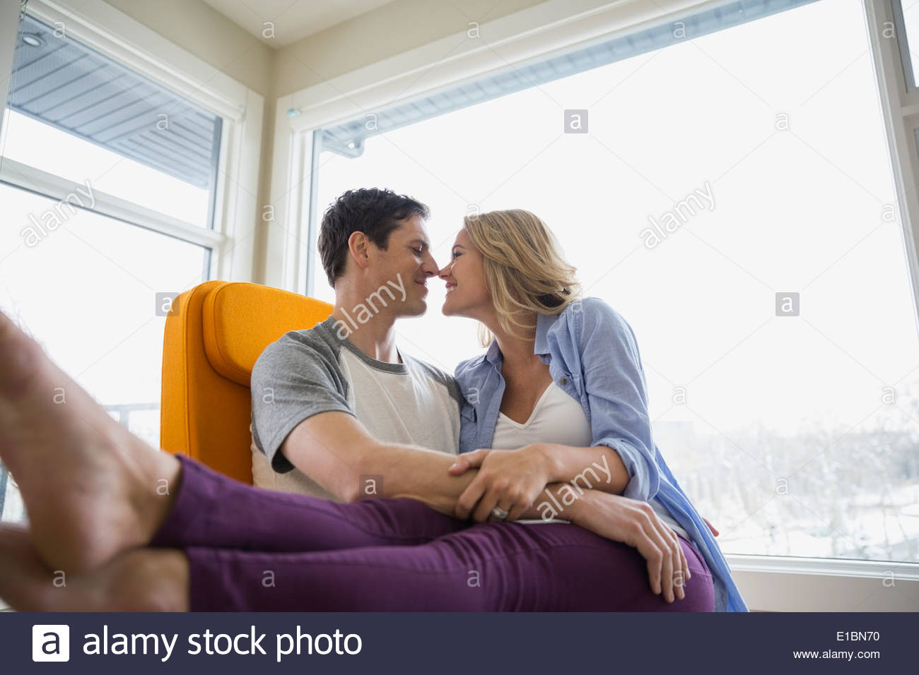 Couple rubbing noses in living room - Stock Image