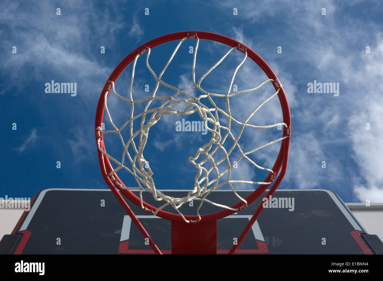 New basketball hoop from below against a cloudy sky Stock Photo
