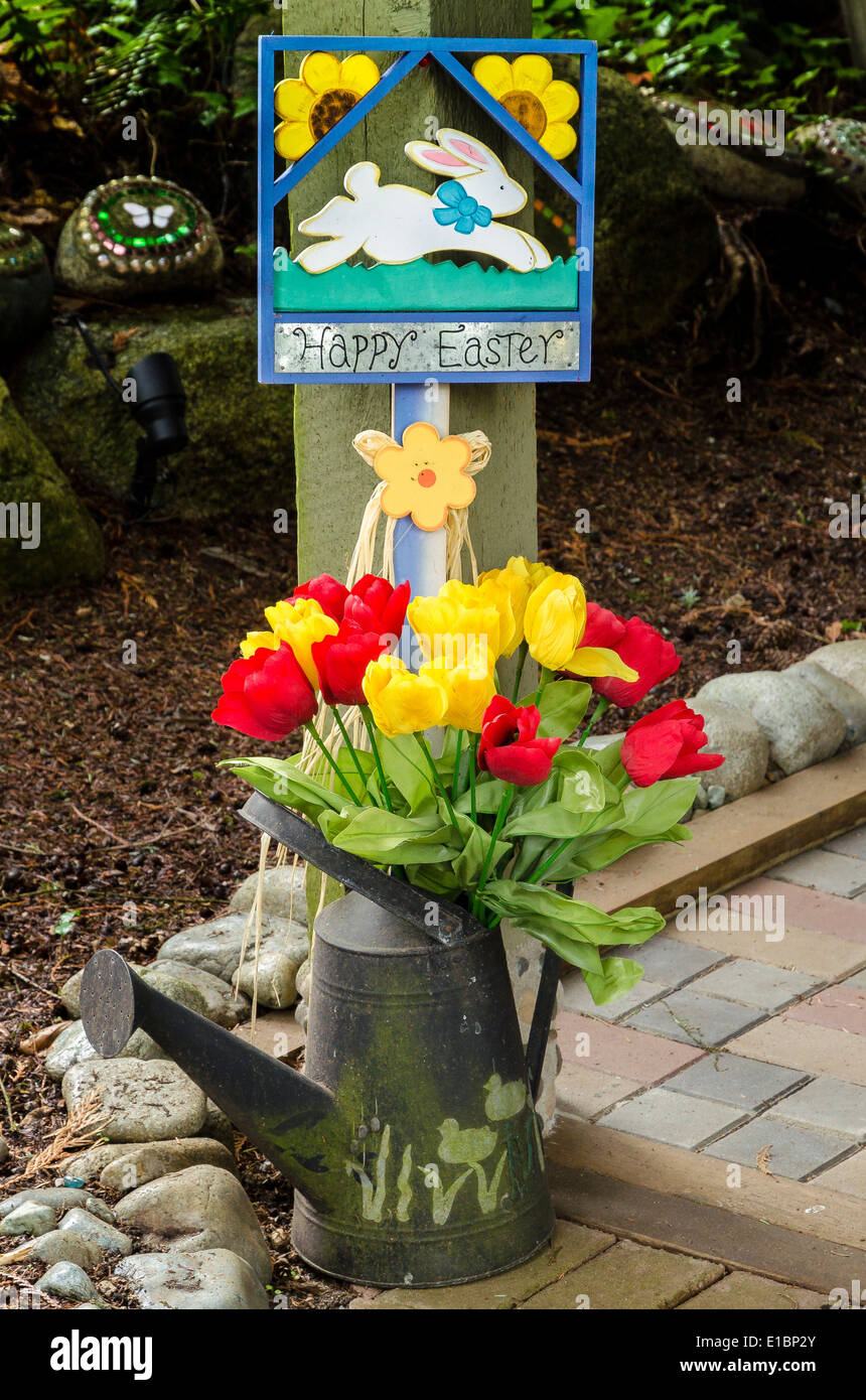 A whimsical front yard decorated for Easter with watering can and tulips. - Stock Image