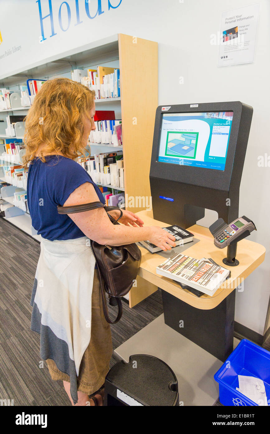 Woman in library using automated check out machine, Vancouver, British Columbia, Canada - Stock Image