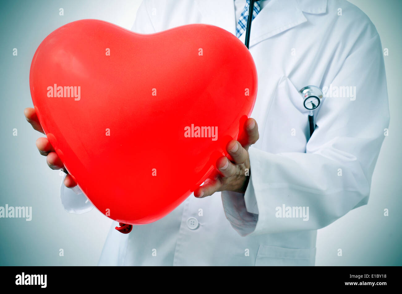 a doctor holding a red heart-shaped balloon, symbolizing the cardiovascular medicine - Stock Image