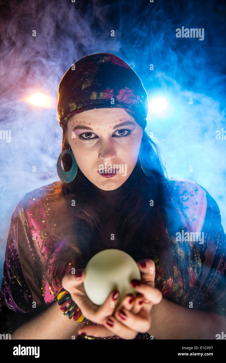 a mystic woman gypsy Fortune teller holding a crystal ball looking into the future - Stock Image