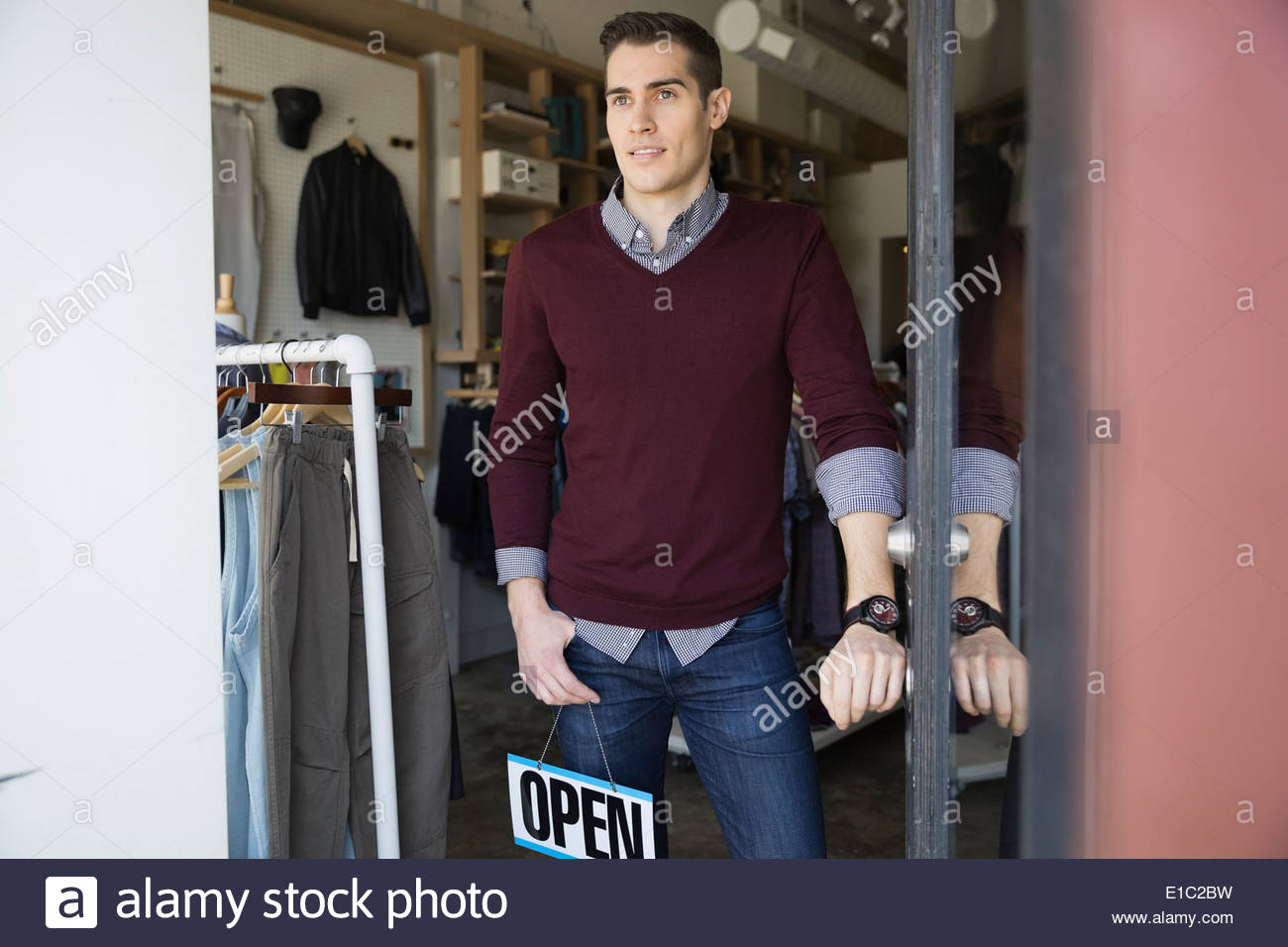 Business owner with Open sign in shop doorway Stock Photo