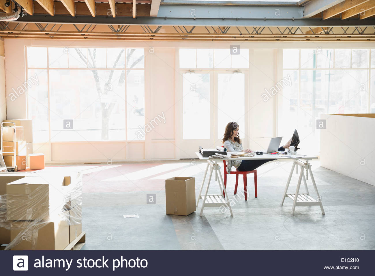Businesswoman with feet up on desk in office - Stock Image