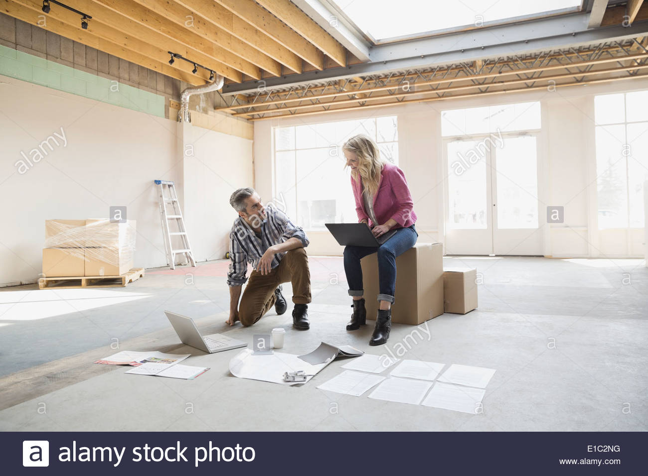 Business people using laptops in new office - Stock Image