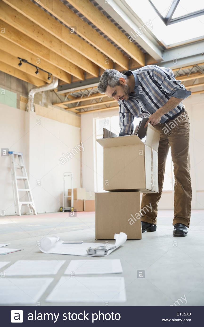 Businessman unpacking cardboard box in new office - Stock Image
