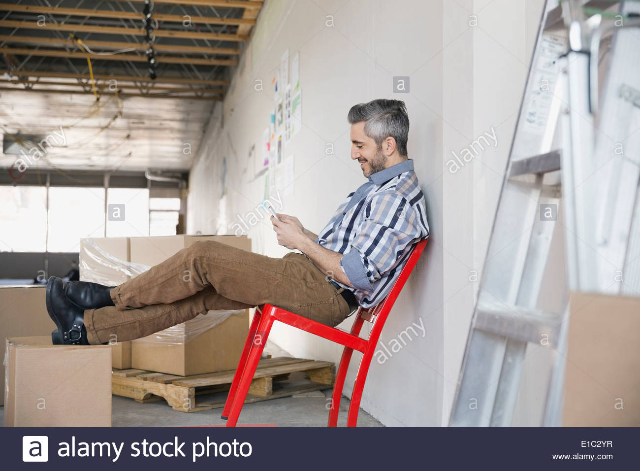 Businessman using cell phone in new office - Stock Image
