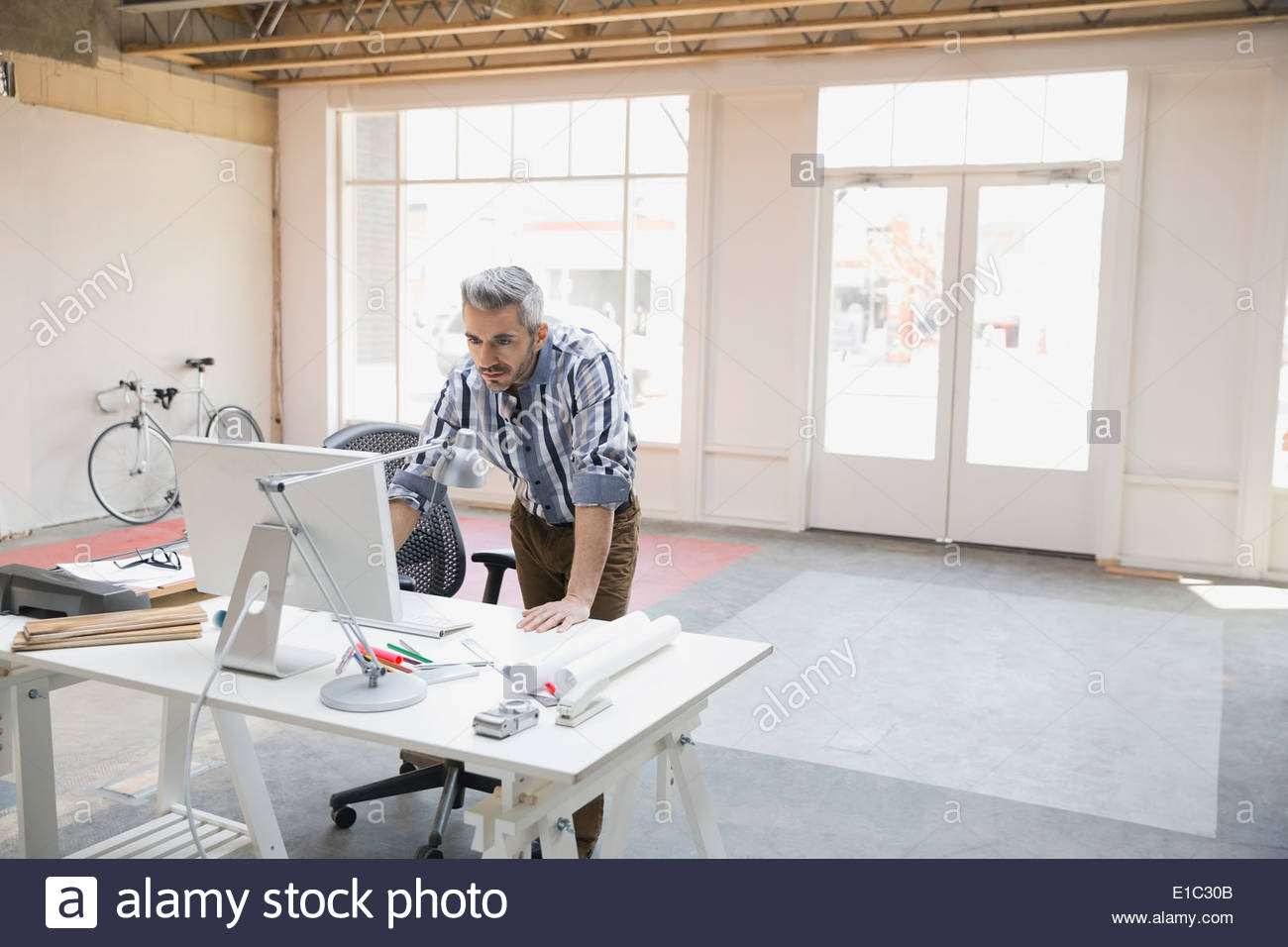 Businessman working at computer in new office - Stock Image