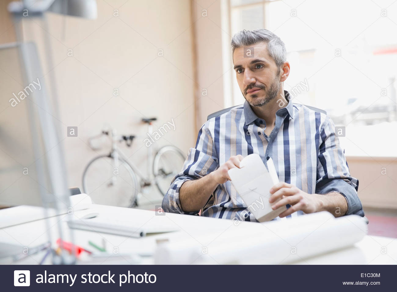 Businessman eating take out food in new office - Stock Image