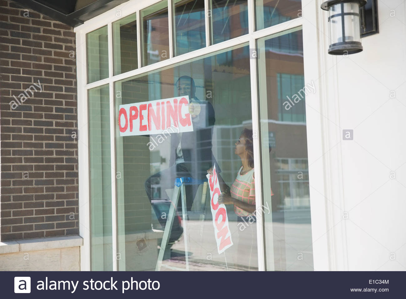 Business owners hanging Opening sign in shop window - Stock Image
